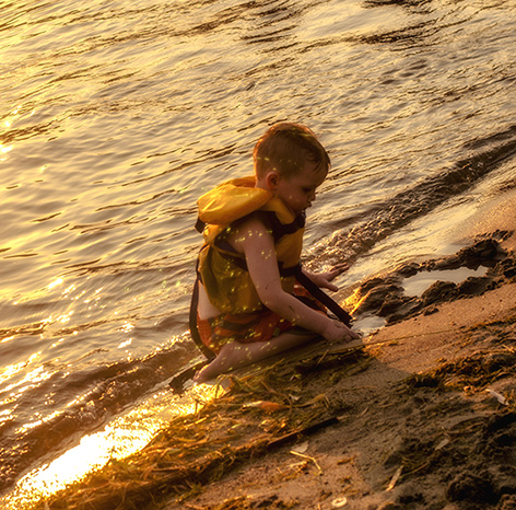 Little boy playing alone on the beach at dusk